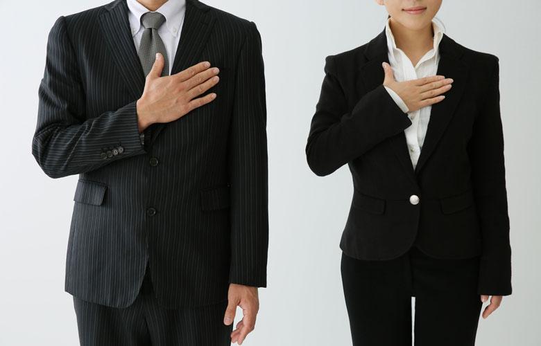 胸に手を当てるスーツ姿のスタッフ