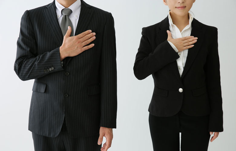 胸に手を当てるスーツ姿の男女